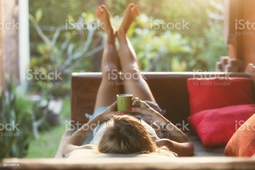 Girl drinking coffee / tea and enjoying the sunrise / sunset in garden. royalty-free stock photo