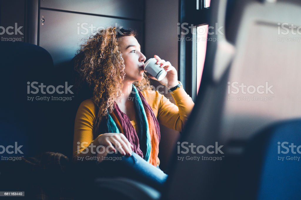 Chica bebiendo CoffeeWhile desplazamientos en tren - foto de stock
