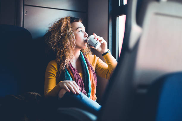 Menina, bebendo CoffeeWhile pendulares de comboio - foto de acervo