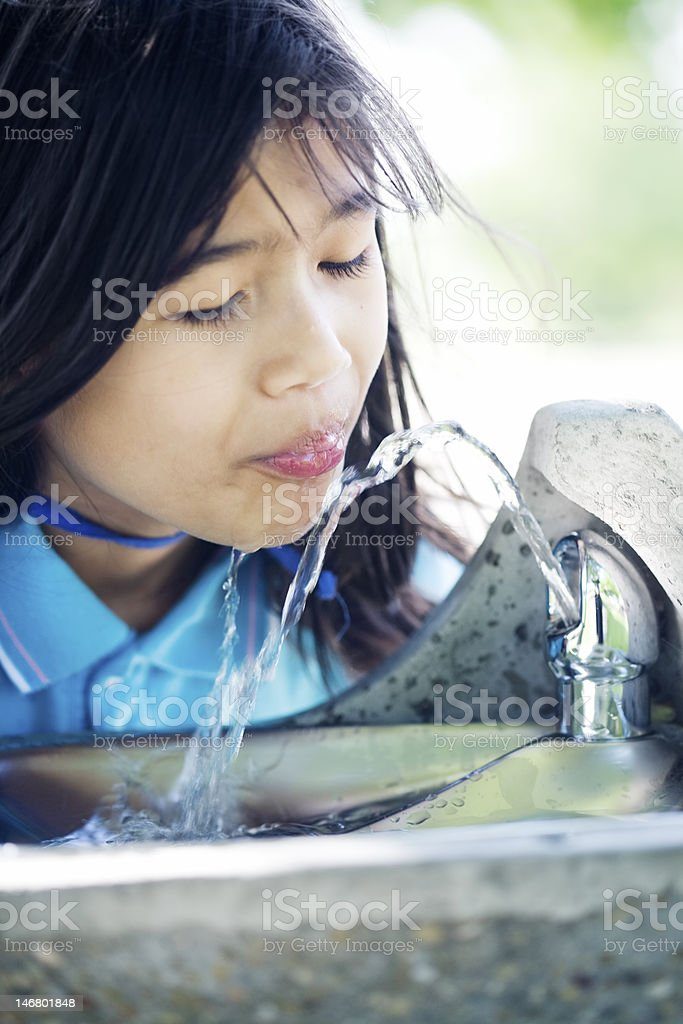 Girl drinking from water fountain stock photo