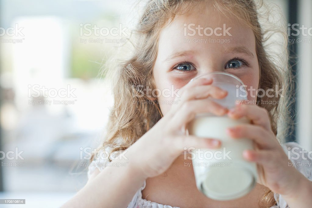 Girl drinking glass of milk stock photo