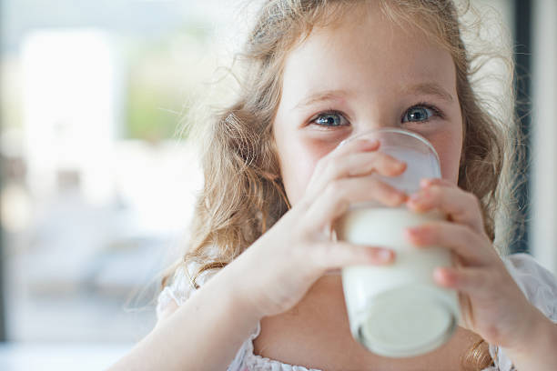 girl drinking glass of milk - kalcium bildbanksfoton och bilder