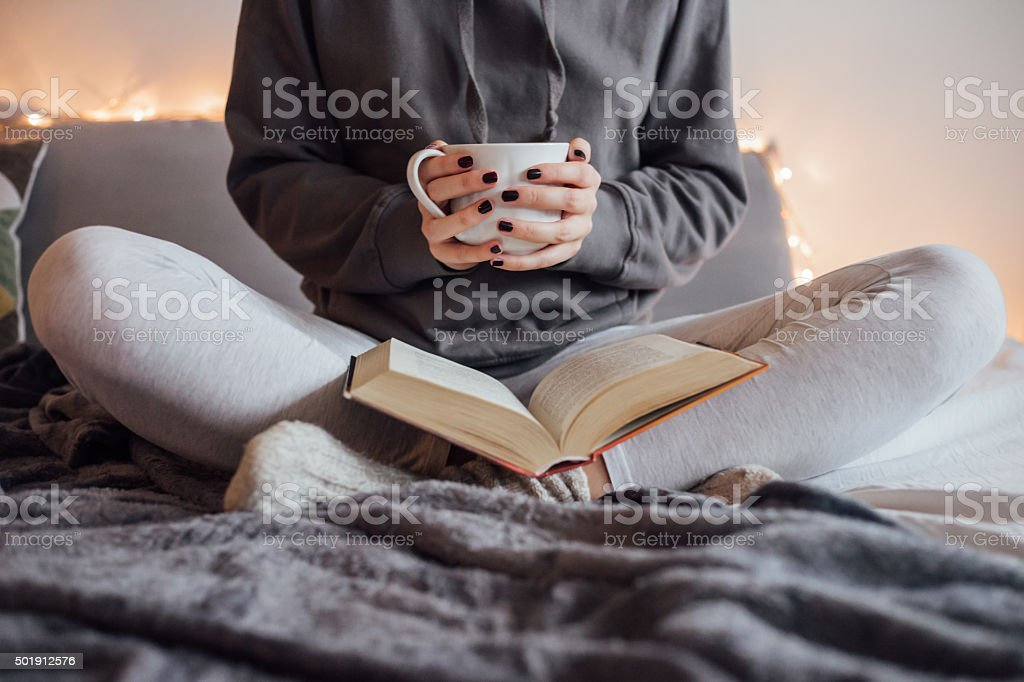 Girl drinking hot tea and reading book in bed stock photo