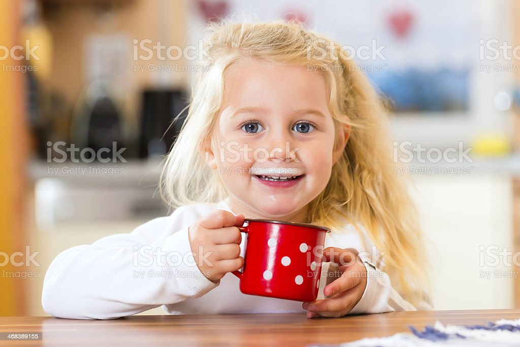 Girl drinking milk in kitchen stock photo