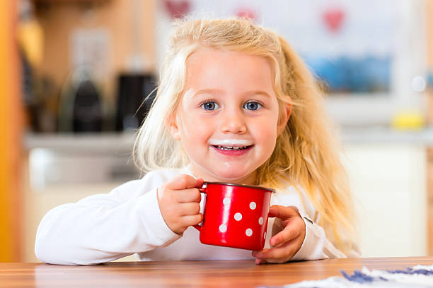 Girl drinking milk in kitchen stock photo