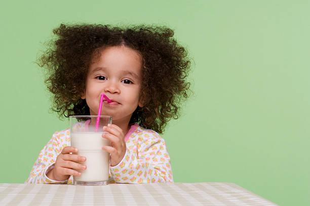 mädchen trinkt milch - farbiges glas stock-fotos und bilder