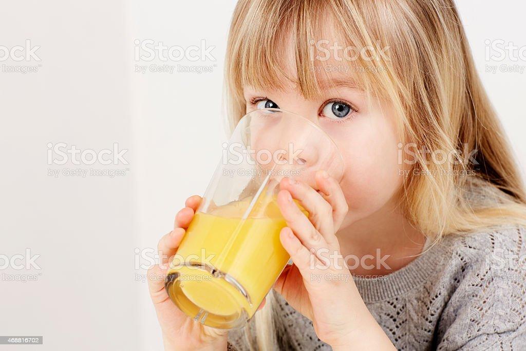 Dziewczyna pije Sok pomarańczowy – zdjęcie