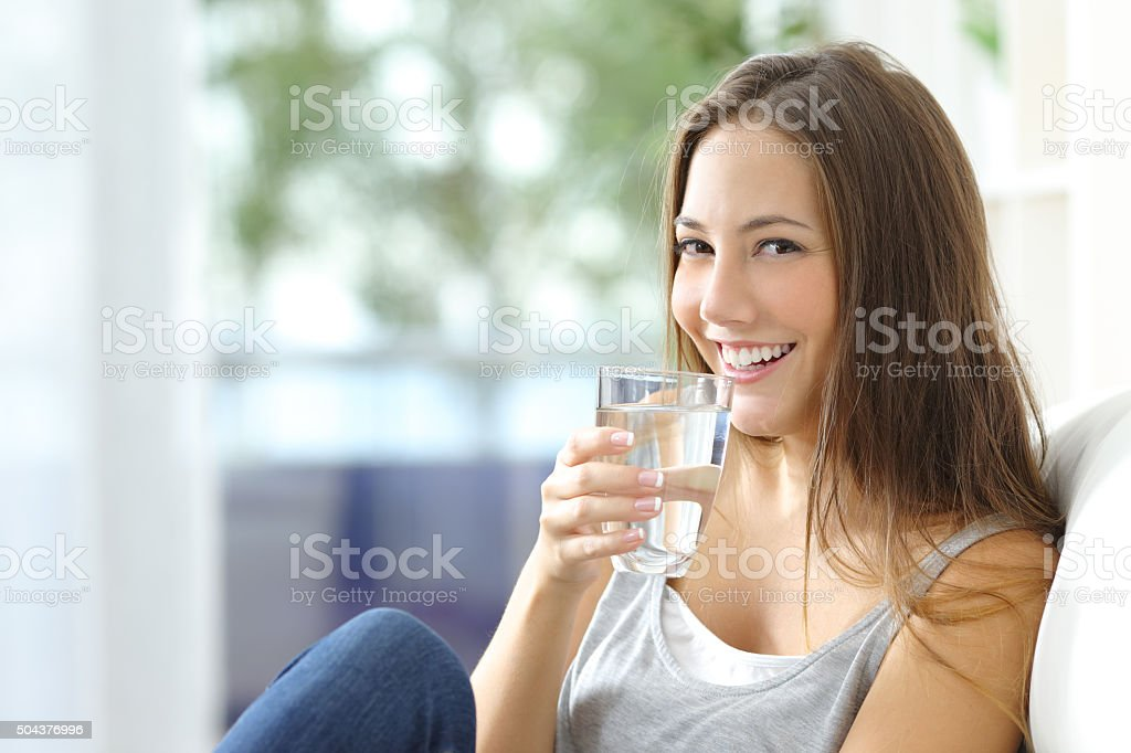 Girl drinking water at home stock photo