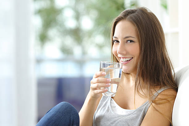 girl drinking water at home - drinking water stock photos and pictures