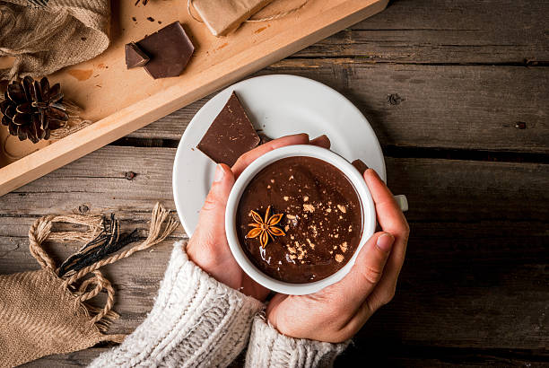 girl drinks hot chocolate mug, with christmas present - hot chocolate stock photos and pictures