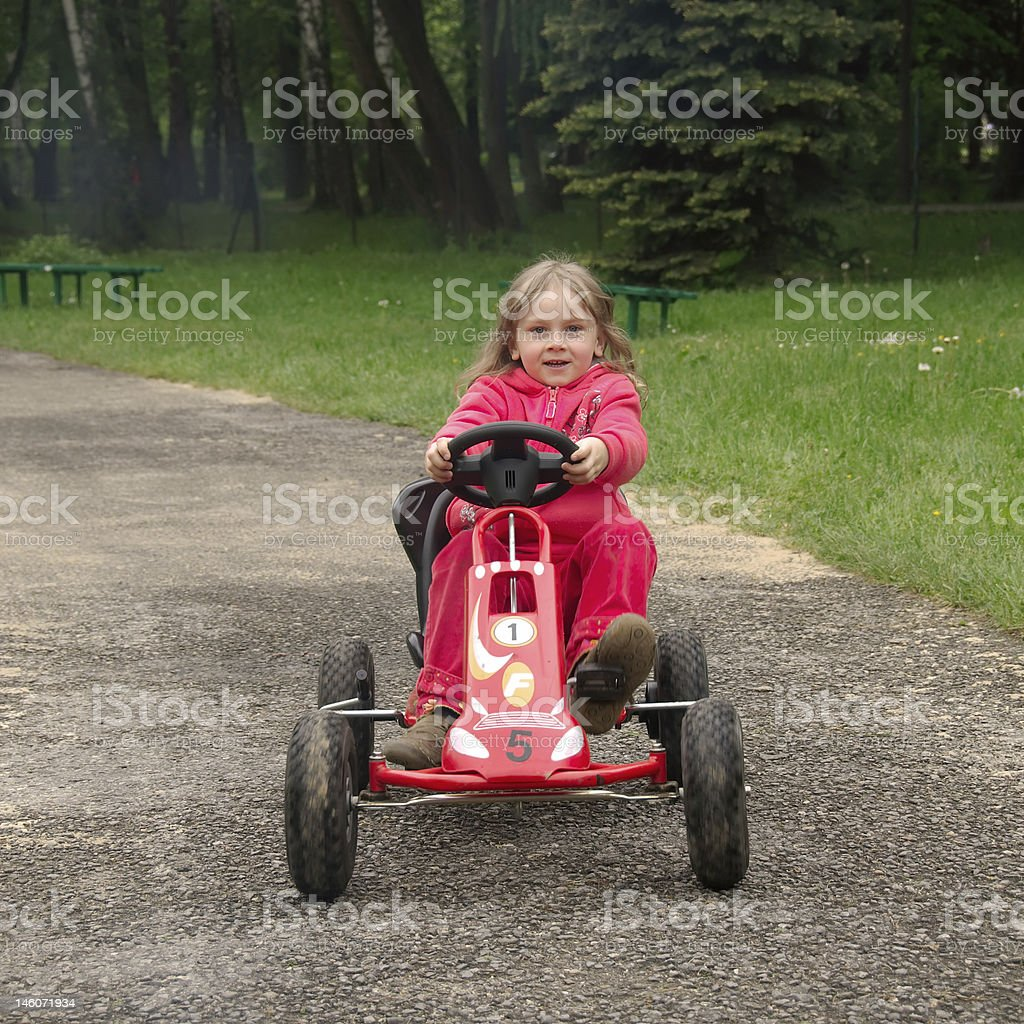 Girl driving a pedal car stock photo