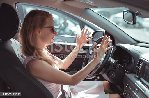 Girl driving car in cabin. Hand gesture accident signal conflict, emotions stress aggression discontent. Pink dress summer in parking lot mall. Misunderstanding scandal and accident on road