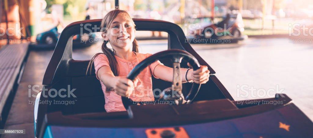Mädchen fahren Elektroautos im Vergnügungspark – Foto
