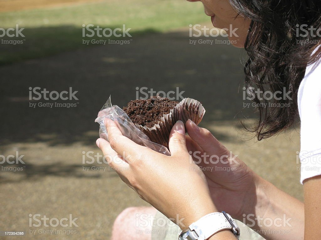 Girl eating a chocolate muffin two hands royalty-free stock photo