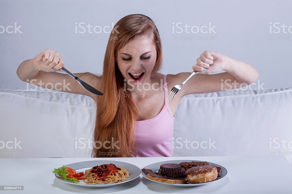 Girl eating a lot of food at once stock photo