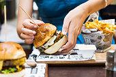 istock Girl eating burger in the restaurant 1034303176