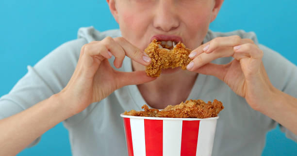 Girl eating chicken wings stock photo