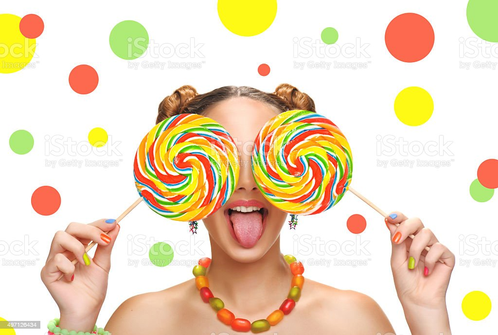 Girl eating colourful lollipop. Lollipop. stock photo