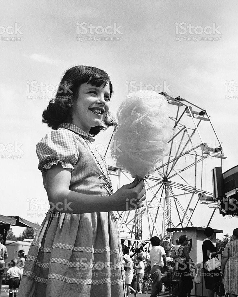 Girl eating cotton-candy at fair royalty-free stock photo