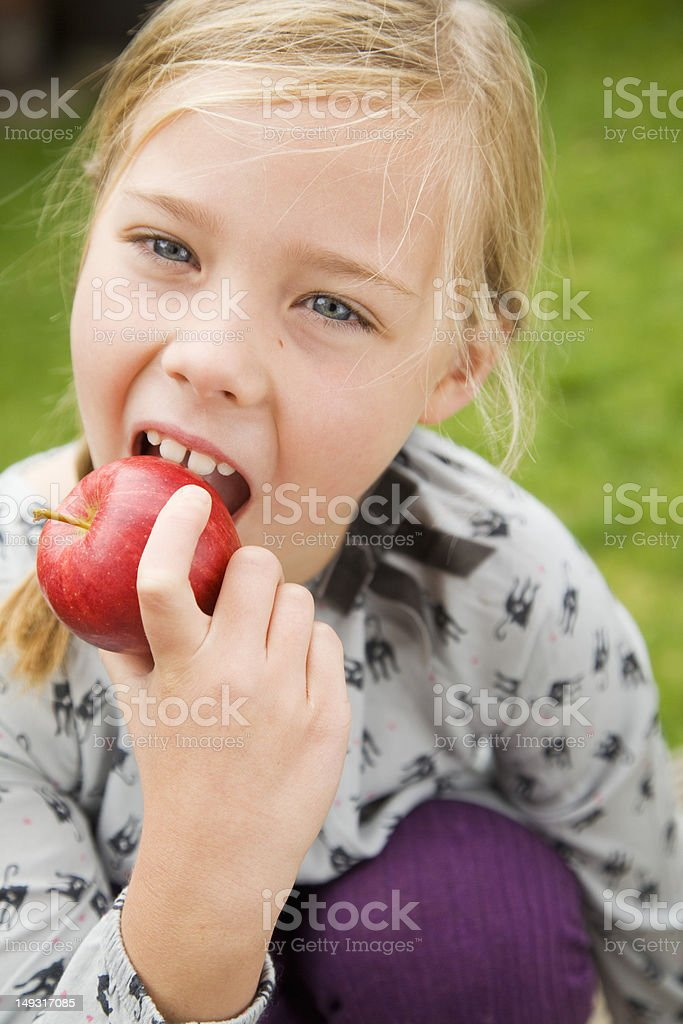 Girl eating fruit outdoors royalty-free stock photo
