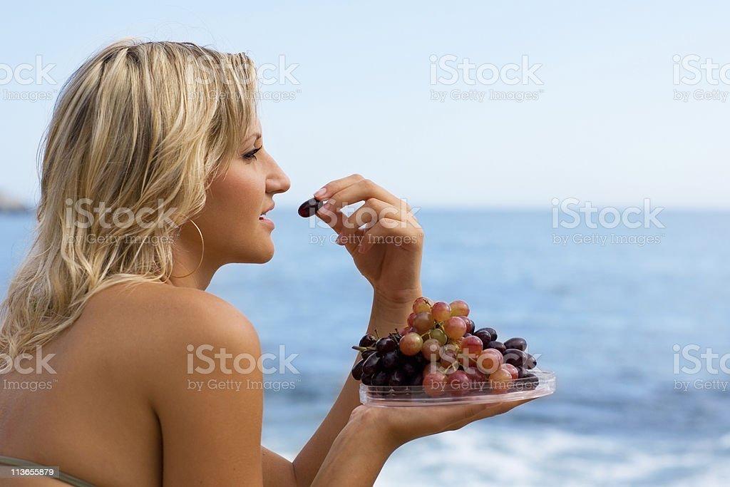 Girl eating grapes at beach by sea. royalty-free stock photo