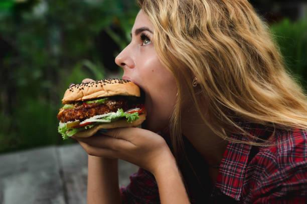 Chica comiendo hamburguesa en el jardín - foto de stock