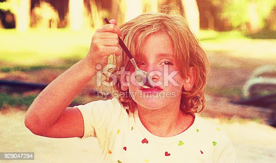 Vintage toned image of a girl eating ice cream with a spoon.