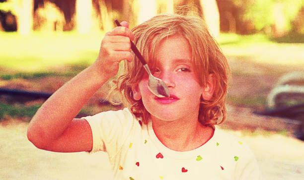 girl eating ice cream outdoors - foto di ice cream foto e immagini stock