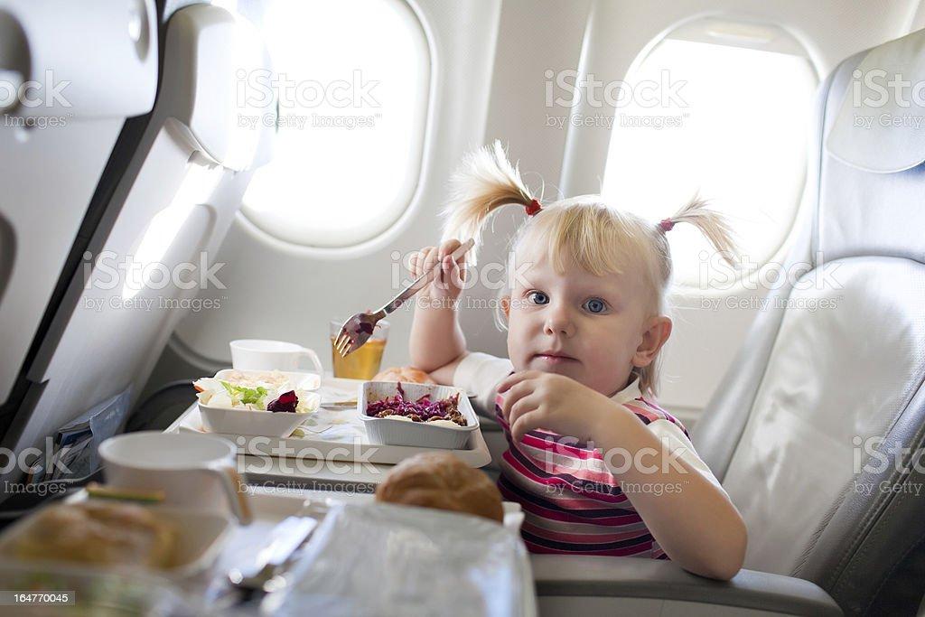 Mädchen Essen im Flugzeug – Foto