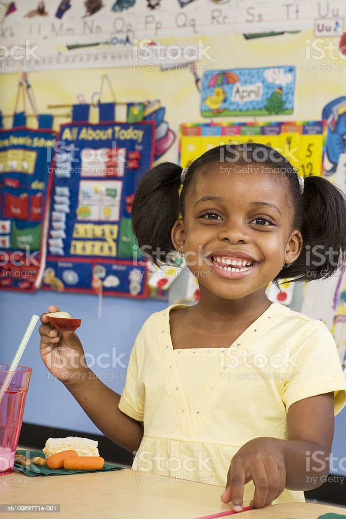 Girl (4-5) eating lunch in classroom foto de stock libre de derechos