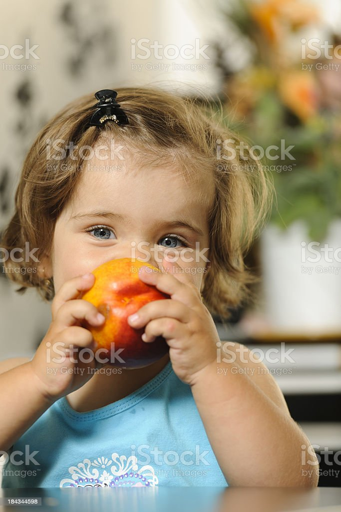 girl eating nectarine stock photo