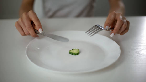 Girl eating one small piece of cucumber, harming health, fear of overweight Girl eating one small piece of cucumber, harming health, fear of overweight anorexia nervosa stock pictures, royalty-free photos & images