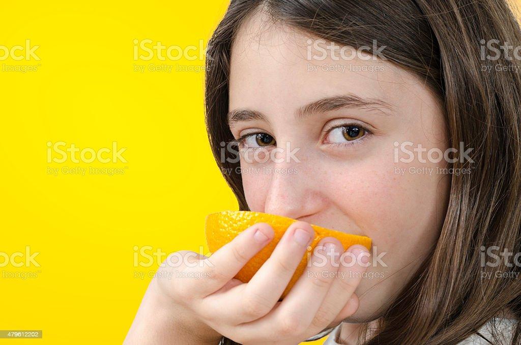 Girl eating orange over orange background. stock photo