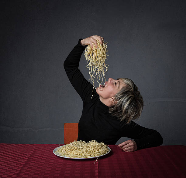 girl eating pasta with hands in a profile view