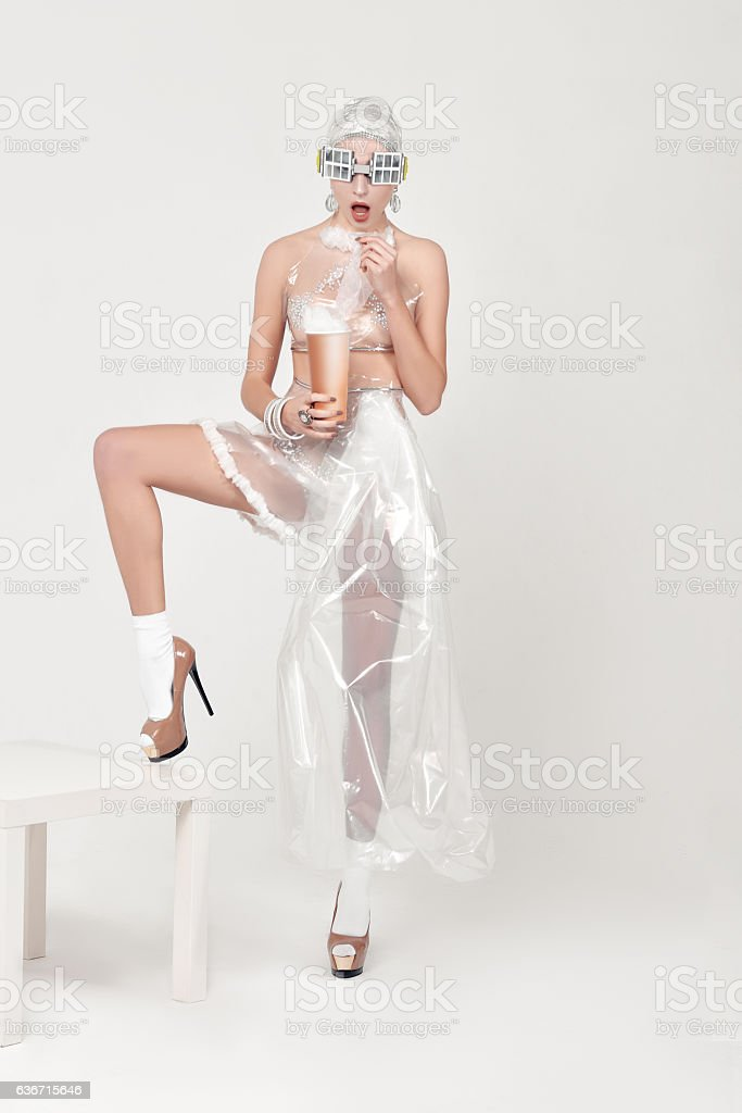 Girl eating plastic from a paper cup stock photo