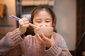 Girl eating rice with chopsticks