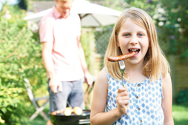 Girl Eating Sausage At Family Barbeque stock photo