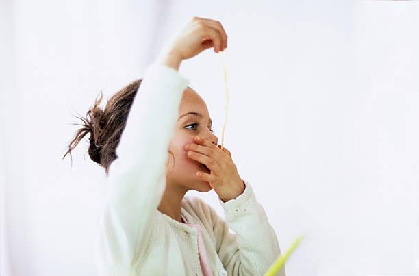 girl (4-7) eating strand of spaghetti, side view - probeessen spiele stock-fotos und bilder