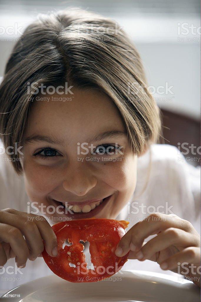 Ragazza mangia di pomodoro foto stock royalty-free