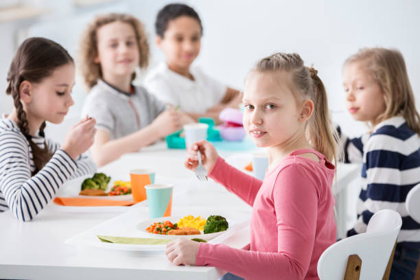 Girl eating vegetables with friends in the canteen during break at picture id960345008?b=1&k=6&m=960345008&s=612x612&w=0&h=8jx5bufdf8hwcfbiqvsvioyd cicpqo7phd 5aybnn4=
