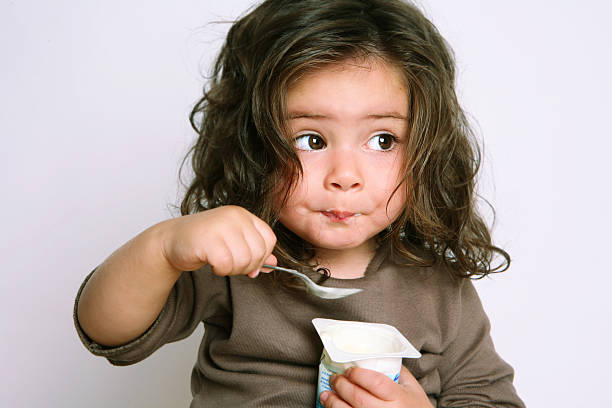 girl eating yogurt stock photo