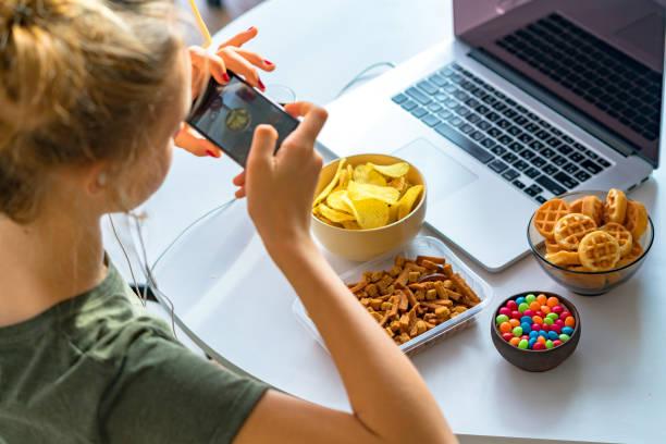 a menina come o fast food e toma fotos dela no smartphone no trabalho. alimentos insalubres: batatas fritas, biscoitos, doces, waffles, cola. comida lixo, conceito. - junk food - fotografias e filmes do acervo