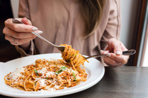 girl eats Italian pasta with tomato, meat. Close-up spaghetti Bolognese wind it around a fork with a spoon. Parmesan cheese stock photo