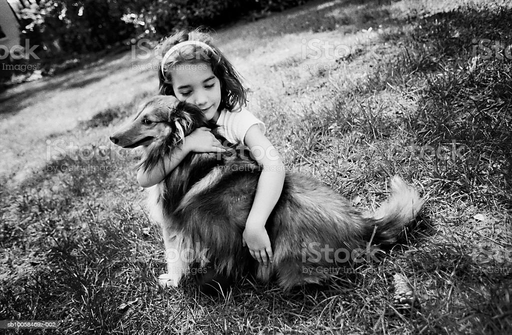 Girl (5-7) embracing dog on lawn (B&W) royalty free stockfoto
