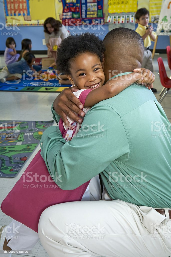 Girl (4-5) embracing father in classroom royalty-free 스톡 사진