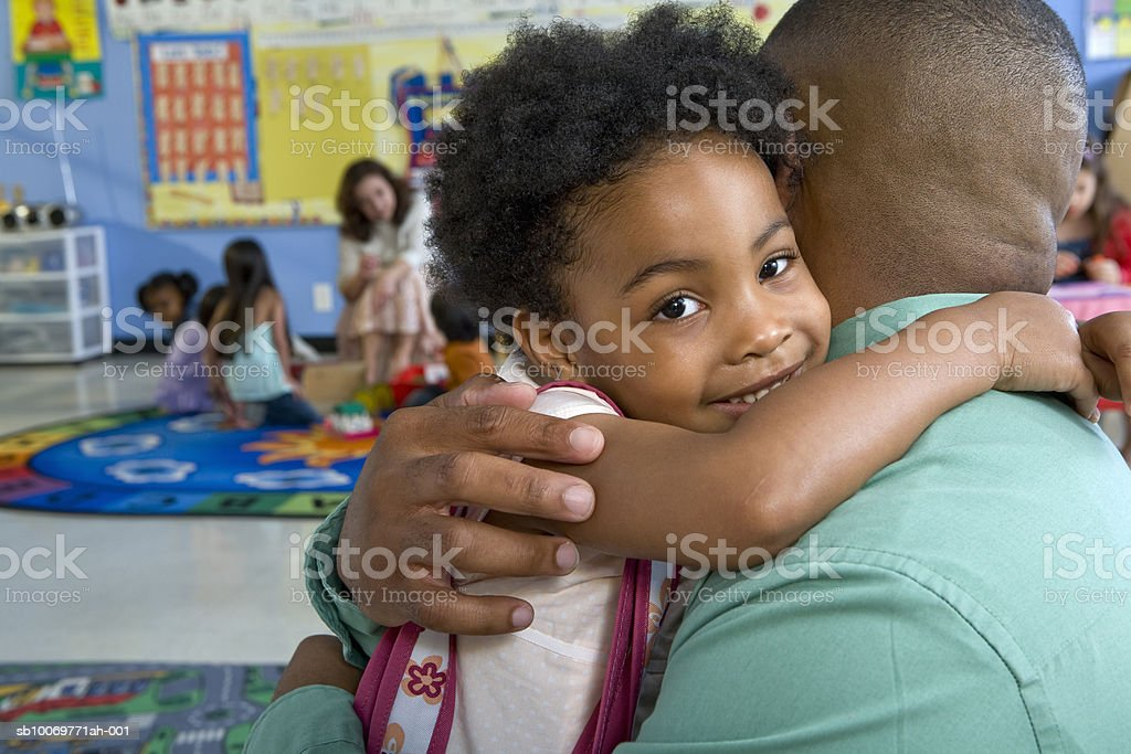 Girl (4-5) embracing father in classroom 免版稅 stock photo