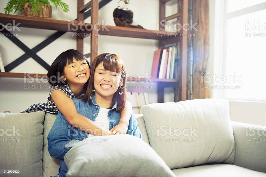 Girl embracing mother at home. stock photo