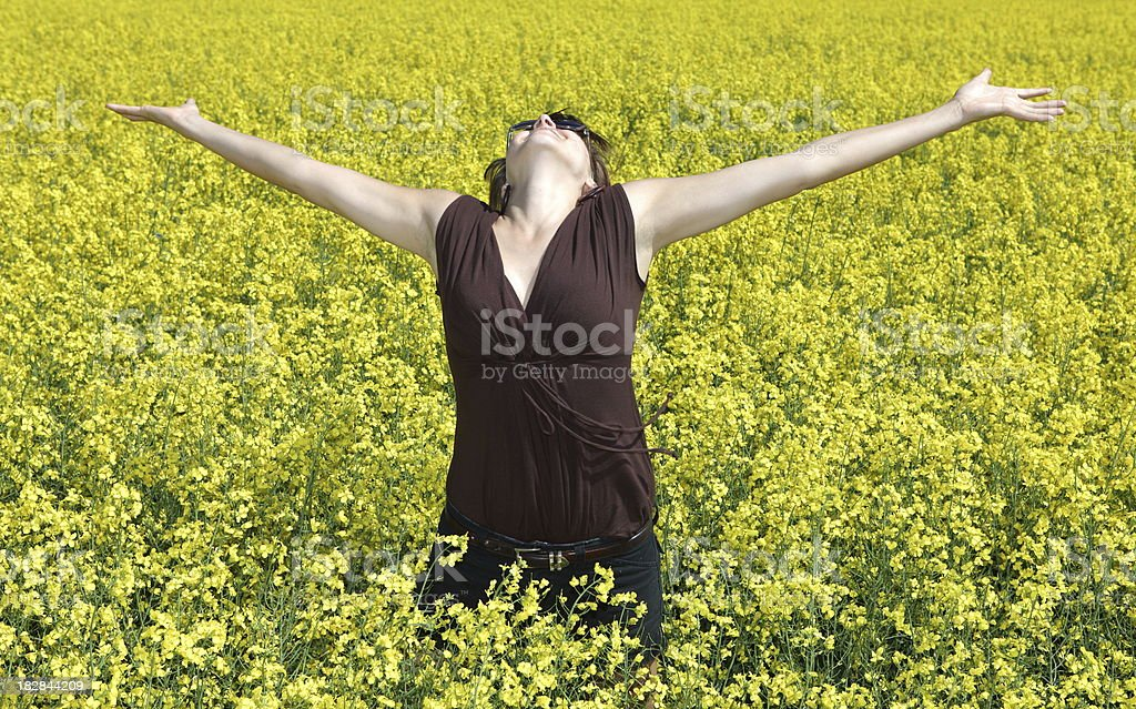 Girl embracing summer in a yellow flower field stock photo