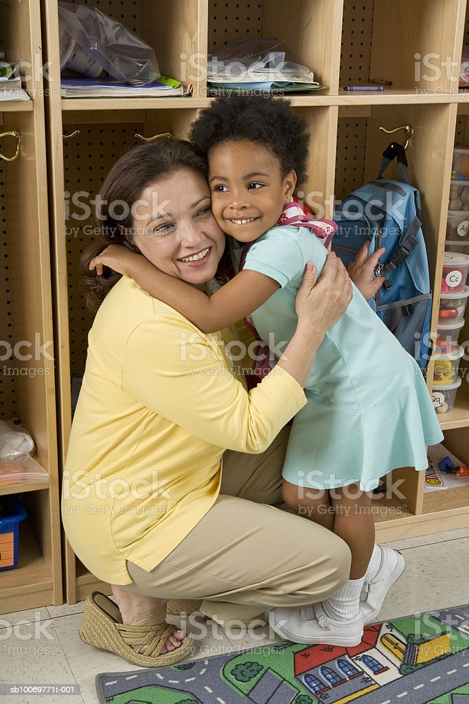 Girl (4-5) embracing teacher, smiling photo libre de droits