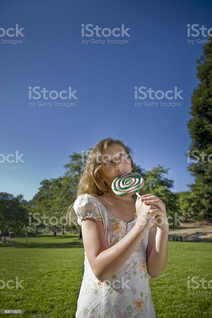 Girl enjoing candy in a park royaltyfri bildbanksbilder